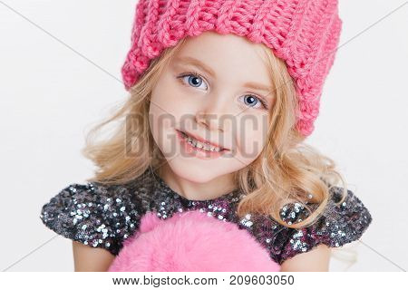 Winter clothes. Portrait of little curly girl in knitted pink winter hat isolated on white. Big blue eyes. Copy-space