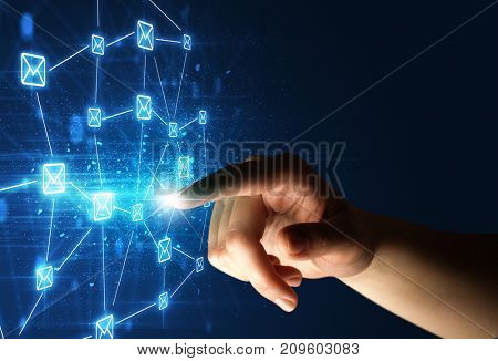 Female finger touching a beam of light surrounded by a blue graphic with envelopes