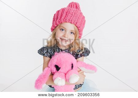 Winter clothes. Portrait of little curly girl in knitted pink winter hat isolated on white. Pink rabbit toy in her hands. Copy-space