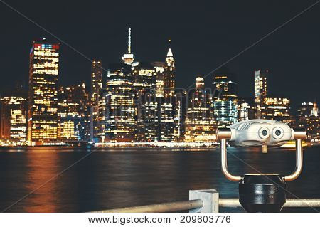 New York City skyline with binoculars at night color toning applied focus on foreground USA.