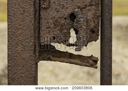 Crashed rusty key hole of the metal wicket. Horror view