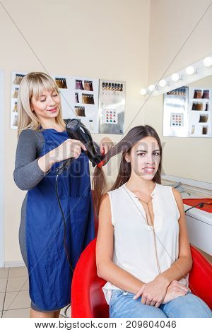 Gorgeous young woman sitting in a chair in a barbershop and a hairstylist dying her long hair on a blurred background. Copy space.