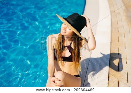 Young lady enjoy sun baths near swimming pool in hotel, resort