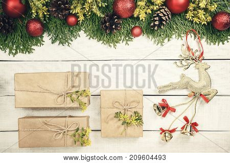 Christmas background with xmas tree red ornaments and on the white wood. Magic deer and gift wrapped craft paper ande decored flower. Top view. Lovely card for wallpaper. Modern floral garland