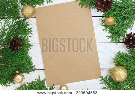 Christmas background with xmas tree golden ornaments and on the white wood desk. Blank craft paper with copy space for invitation. Frame decored twigs of thuja. Top view. Xmas card