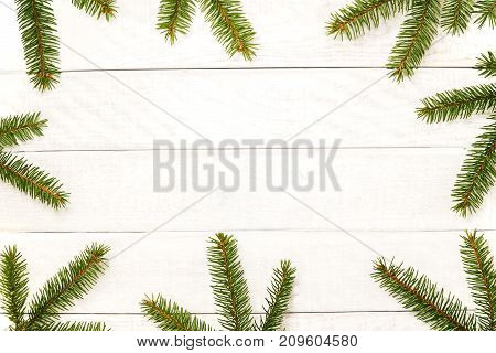 White wooden Christmas background. Border decorated fir branches. Copy space for holiday greetings. lovely xmas festive card. Top view. Flat Happy New Year