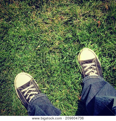 A person with sneakers standing outside in grass.
