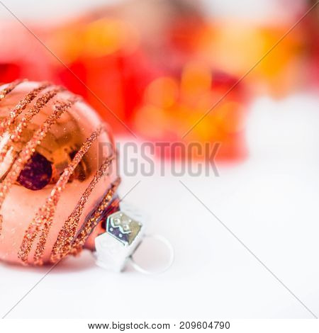 Close-up of xmas ball with blurred colorful Christmas decor in background. Christmas and New Year concept with copy space. Christmas greeting card.