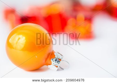 Close-up of yellow xmas ball with blurred colorful Christmas decor in background. Christmas and New Year concept with copy space. Christmas greeting card.