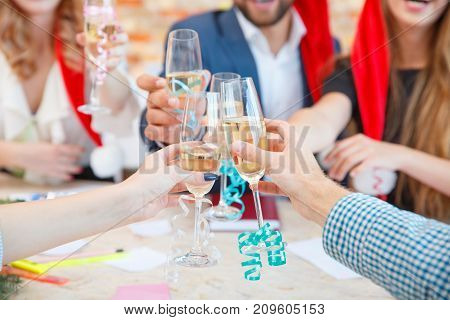 Close-up of successful business company drinking alcohol and celebrating the new year on a blurred office background. Friends toasting wine on Christmas.