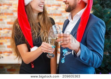 Close-up picture of festive man and woman cheering and clinking glasses on a blurred background. Colleagues drinking at the Christmas party.