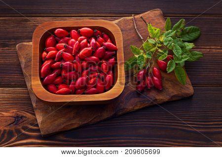 bowl full of dogrose on brown background - herbal medicine