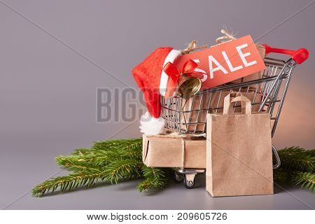 Shopping trolley with gift boxes, tablet with an inscription sale and brenches of fir-tree on a grey background. Christmas and New Year sale.