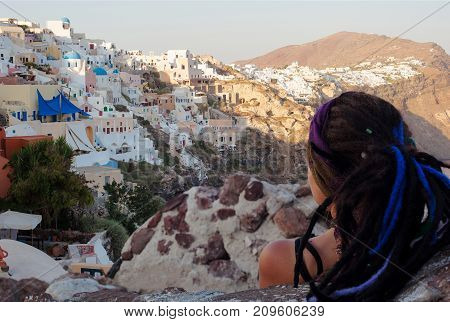 Woman Traveler From Behind Looking At Amazing Sunset Of Oia Village In Santorini