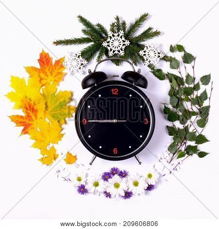 Representing the seasons of the year through the alarm clock and natural material on a white background. Autumn Top view