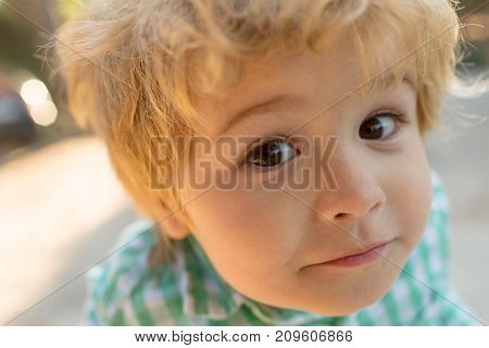 Funny Face Portrait Child Close Up. Face Of Sweet Cute Child, Boy Looks At Camera, Emotionate Expres