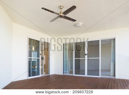 New timber deck with white walls, sliding glass doors and ceiling fan