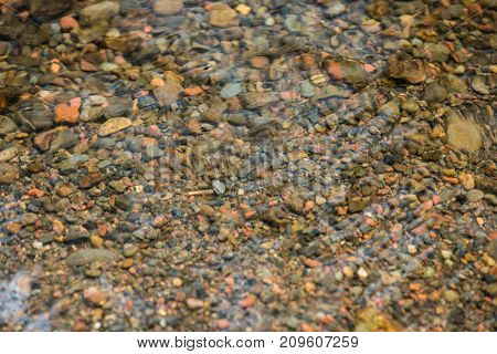 Top view stones in the river. The Rock ground cover water backgrounds. Small pebble stones in creeks.