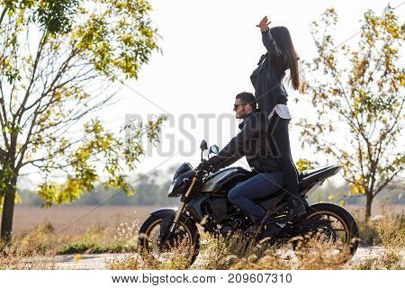 Black, sport motorcycle close-up rides on the road with its owner front view girl standing on motorcycle side view