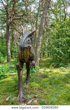 Life sized Allosaurus dinosaur statue in a forest