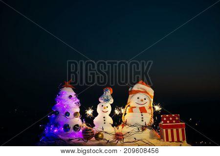 Christmas Night, Celebration Near Christmas Snow Tree. Snow Sculptures At Night. Two Happy Snowmen A