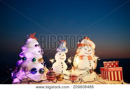 Winter Holidays, Frosty Air In Mountains. Snowmen Surrounded By Snow. New Year's Mood With Bengal Li