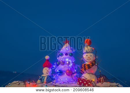 Blue Christmas Background. Snowmen Outside During Cold Winter Weather. Happy Snowmen In Christmas Ev