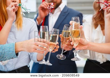 Close-up of a company of young friends celebrating Christmas, having fun and clinking champagne drinks on a blurred office background.