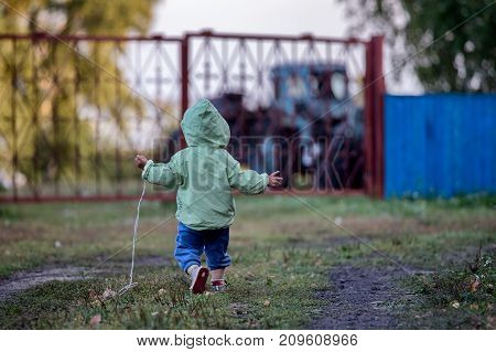 A two year old kid in a coat with a hood is running on the grass towards a tractor parked outside the metal fence. Kid's arms are raised up and to the sides. Back view. Background is blurred.