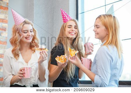 Smiling office lady, at lunchtime and eating pizza. Festive atmosphere. Girls in holiday caps on their heads.