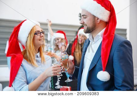 Gorgeous and successful business people in festive Santa hats drinking champagne and celebrating Christmas on the blurred office background.