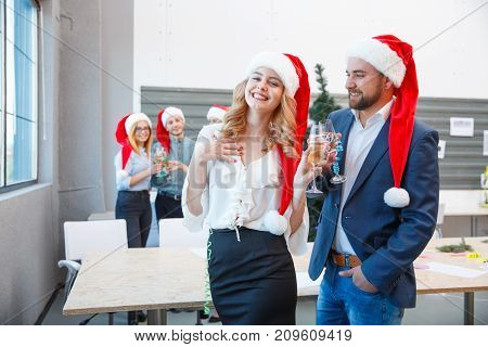 Happy business people in Santa Claus hats celebrating on a blurred office background. Workers drinking champagne at the Christmas party.