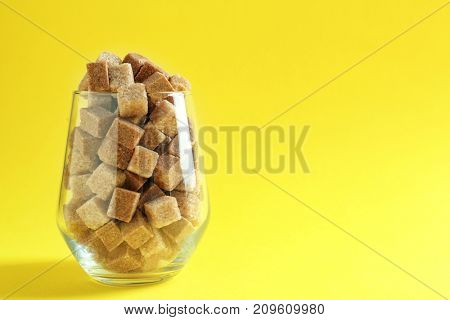 Glass full of brown sugar cubes on color background