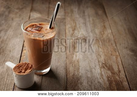 Glass with protein shake and powder in scoop on wooden table