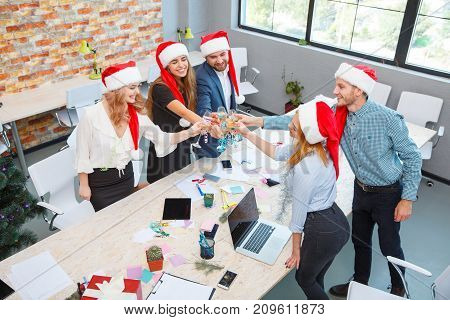 Handsome men and smiling women in red Santa caps cheering and toasting with glasses of alcohol on Christmas on a blurred office background.