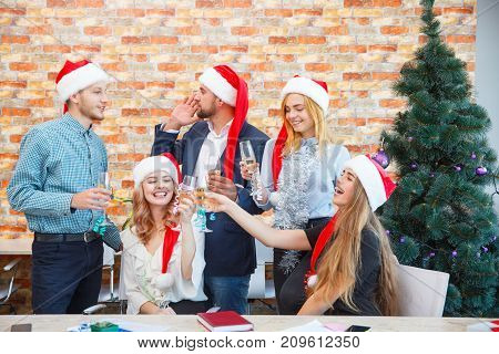 Attractive cheerful coworkers having fun and drinking at the Christmas event on a blurred office background. Business colleagues in red Santa hats.