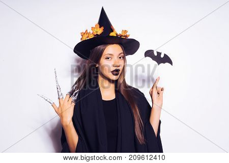 a young sexy mysterious girl dressed in a witch, celebrates halloween, in a big black hat, adorned with yellow leaves