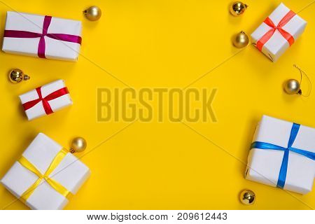 top view of a box with gifts in white wrapping paper on a yellow background.