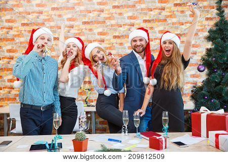 Beautiful business company celebrating Christmas or New Year with red Santa hats and glasses of alcoholic drinks on a blurred office background.