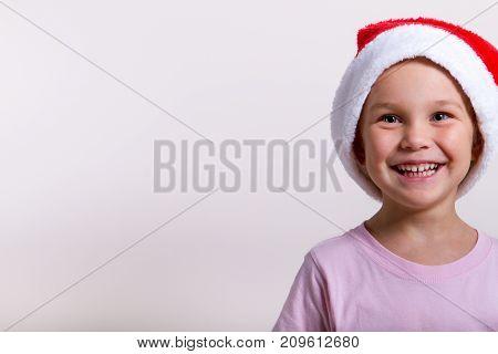 portrait of a little smiling blonde girl in santa hat