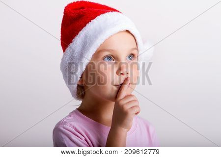 portrait of a little smiling blonde girl in santa hat, holding finger near lips, showing to don't speak loudly.