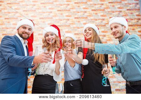 Group of positive people celebrating New Year in santa hats with fun and amazing bengal lights or sparklers on a blurred office background.