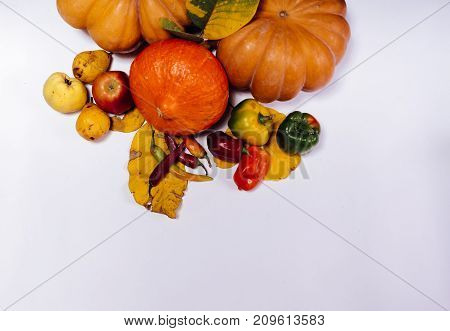 composition for decorating a house for halloween, on a white table lie yellow and orange pumpkins, yellow and red apples, peppers and autumn leaves
