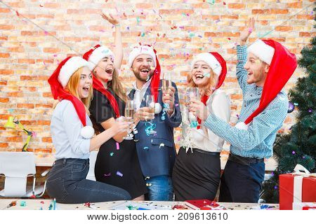 Gorgeous business colleagues throwing colorful fun confetti and drinking champagne on a Christmas night on a blurred office background.