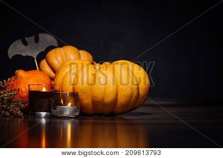 a composition for decorating a house for halloween, lie yellow and orange pumpkins, candles burn