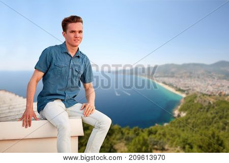 Smiling man in denim clothes sits on edge of building roof near sea shore