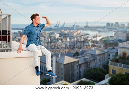 Young man in looks afar, sits on edge of roof in seaport, collage