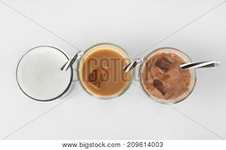Glasses with protein shakes on white background