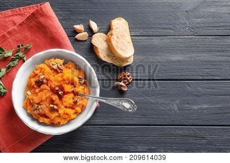 Bowl with mashed sweet potato on wooden background