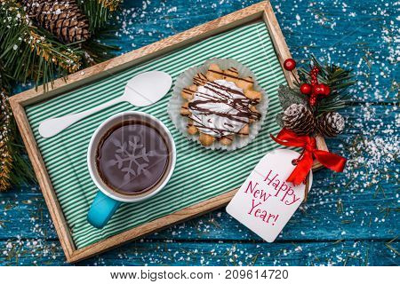 New Year's photo of tea, cake on table with spruce branches, postcards with Christmas wishes